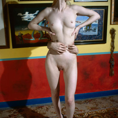 Nude female with disembodied hands around her waist.