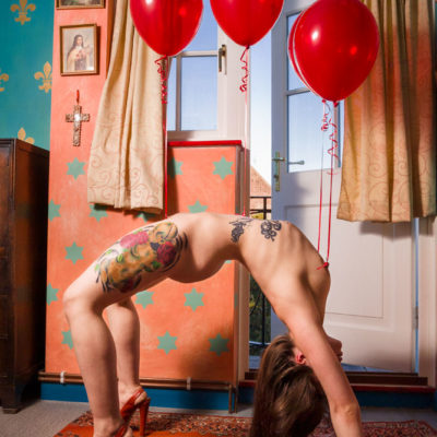 Nude with four red helium balloons attached to her piercings doing crab