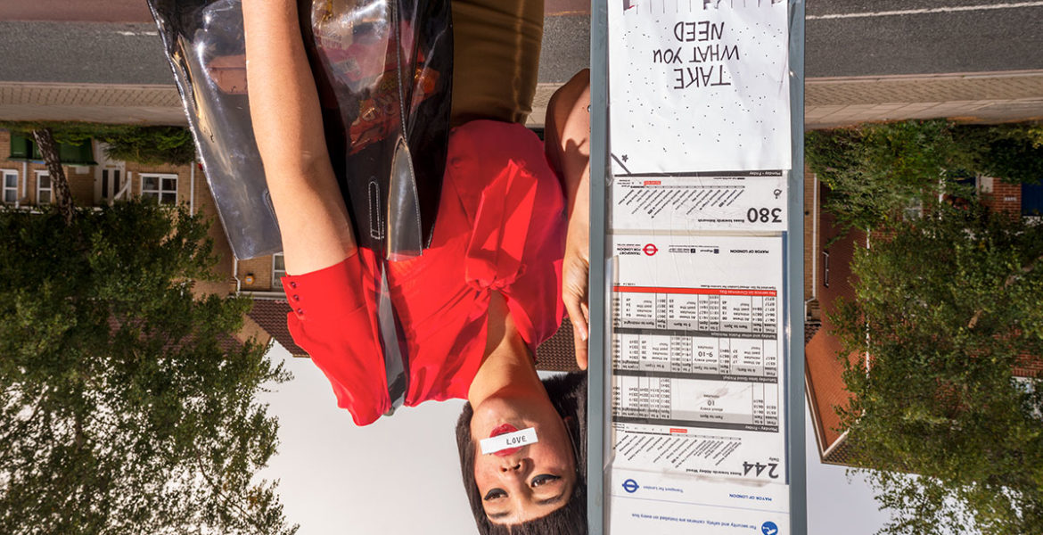Upside down photo of woman at bus stop